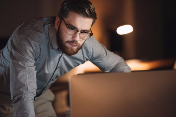 graphicstock image of concentrated designer dressed in shirt and wearing eyeglasses working late at